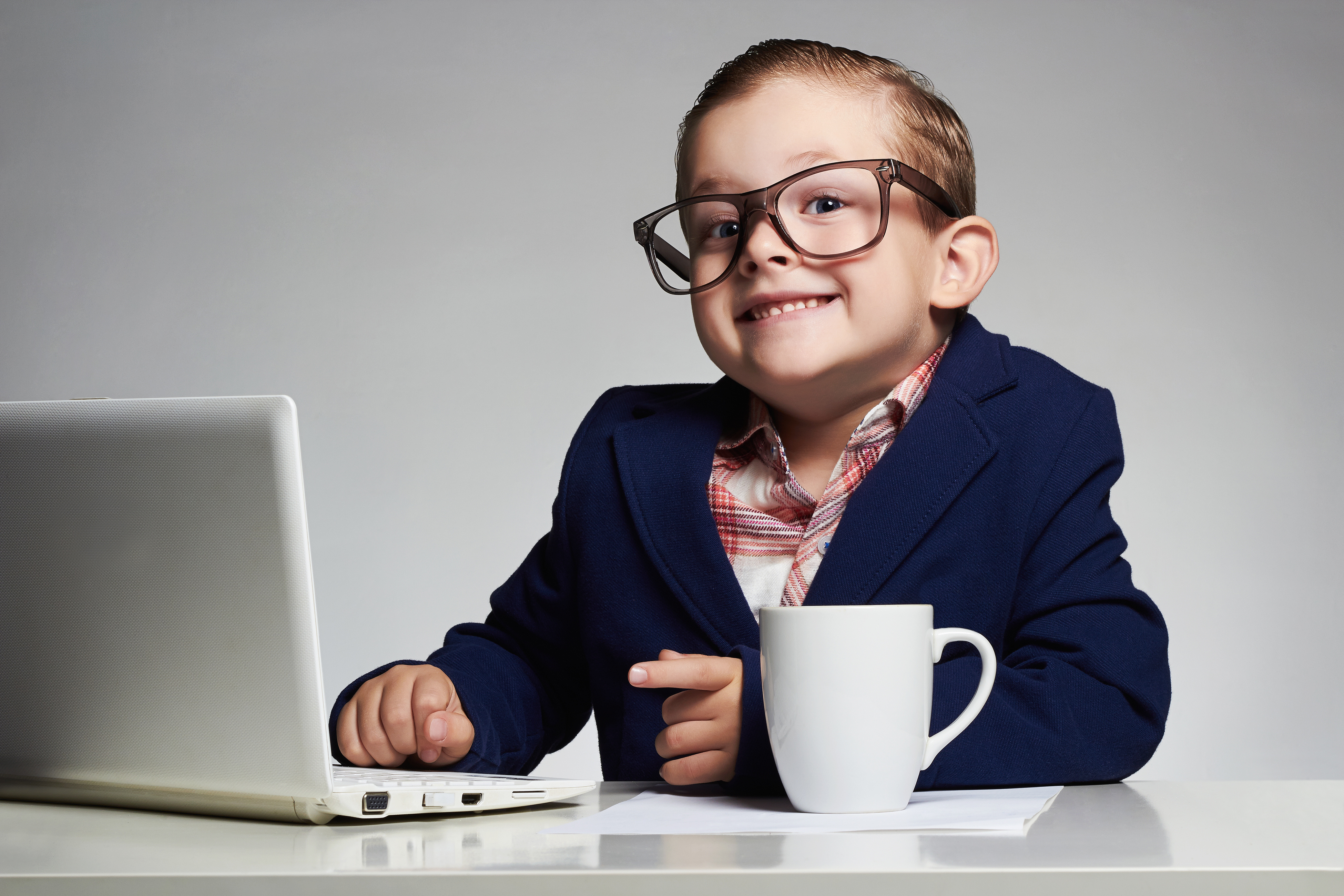 funny child with computer.Young business boy. smiling kid