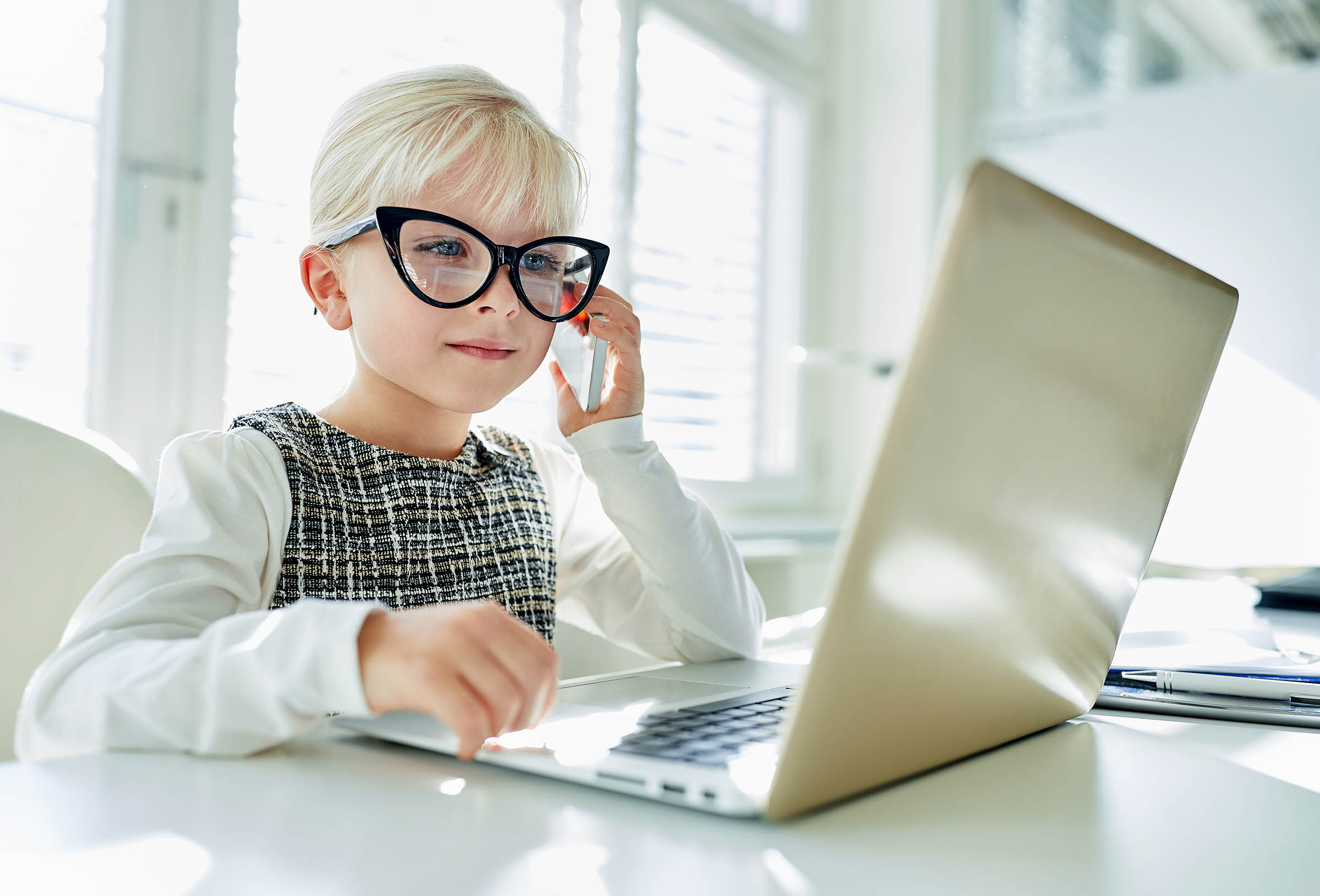 Litttle girl looking at laptop screen with expression of surprised and excitement. Smart, smilling little girl taking notes . Communication in business concept.